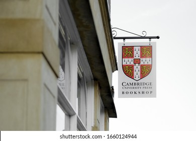 Cambridge, UK - Circa February 2020: Iconic University coat of arms seen on signage located outside a famous bookshop, located in central Cambridge. Part of the ornate, sandstone building is seen.