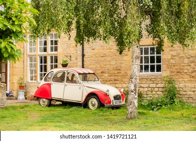 Cambridge, UK - Circa June 2019: Popular, classic french car seen parked at the entrance to a large manor house during summer. Part of the stone brick work and weeping tree can be seen near the car.