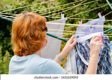 Cambridge, UK - Circa June 2019: Woman seen hanging freshly laundered clothes on a rotary clothes line in a garden. Various adult garments can be seen looking to be dried, before ironing.