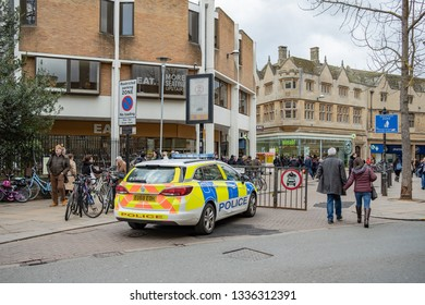 Cambridge, UK - Circa March 2019: Police emergency response vehicle seen parked near a busy Saturday shopping area in the town centre. Many people can be seen walking around the various shops.