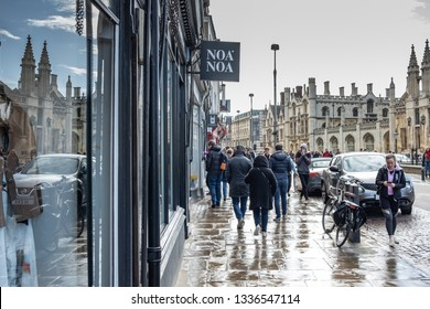 Cambridge, UK - Circa March 2019: After a heavy down pour, shoppers and tourists can be seen walking the pavement. The famous Kings College can be seen in the distance and various shops.