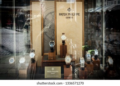 Cambridge, UK - Circa March 2019: Jewellery window display of expensive, swiss made analogue watches in individual plinths. Seen through glazing, tasteful reflection of a nearby street can be seen.