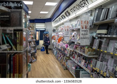 Cambridge, UK - Circa March 2019: Woman seen browsing the stationary section of a well known, British magazine and stationary seller. A large selection of books and stationary items are seen displayed