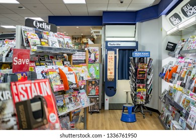 Cambridge, UK - Circa March 2019: Shallow focus of many different types of magazines seen on multiple shelving at a well known book store. The background shows part of a Passport ID photo booth.