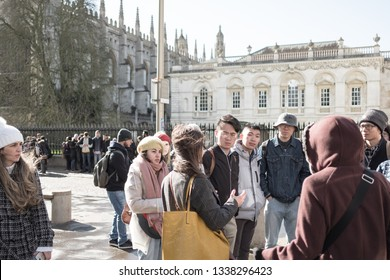 Cambridge, UK - Circa March 2019: Group of young Chinese tourists seen in a group outside the famous Kings College. The tourists are being given a talk by a local guide about the history of the city.