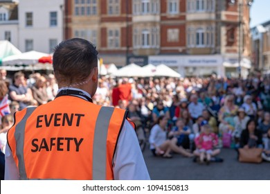 Cambridge, UK - Circa May 2018: Shallow focus of an Event Safety officer seen facing members of the public in a town square. The public are watching the Royal Wedding on a large, outside screen.