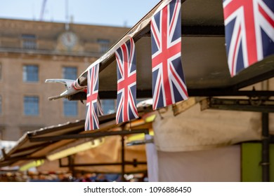 Cambridge, UK - Circa May 2018: Shallow focus image of a Union Jack flack on a row on flag bunting, above a market stall. Part of a bank holiday celebration in the UK in early summer.