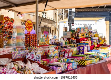 Cambridge, UK - Circa May 2018: Wide variety of candies and other well-known products seen on display at an open air market stall. The stall has just recently been opened, waiting for customers.