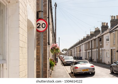 Cambridge, UK - Circa September 2019: Terraced street showing a 20mph speed limit sign. The historic, old houses are seen together with parked vehicles. often used as a busy commuter road.