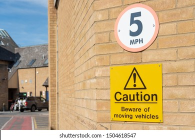 Cambridge, UK - Circa September 2019: Shallow focus of a 5 MPH and caution sign seen at the back of a retail shopping arcade in the English city. A distant worker is seen having a break.