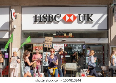 Cambridge, UK - Circa September 2019: Extinction Rebellion protestors seen outside a famous high street bank. Some protestors have locked themselves inside the branch, with signs stuck to the glass.