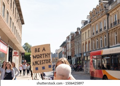 Cambridge, UK - Circa September 2019: Woman Extinction Rebellion protestor seen holding a makeshift Climate Change banner outside a well-know High Street bank. Seen talking to a member of the public.