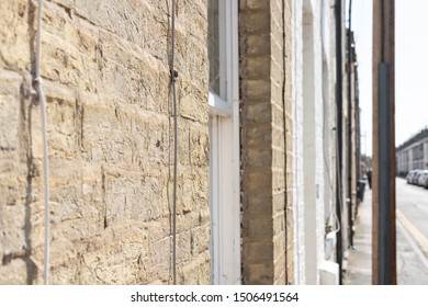 Cambridge, UK - Circa September 2019: Shallow focus of the rough, textured surface of an exterior wall on a terraced house down a narrow street. Telephone cables can be seen nailed to the wall.