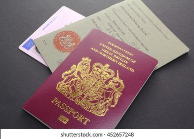 CAMBRIDGE, UK - JULY 14, 2016: United Kingdom or British EU Passport with International Driving Permit and Driving Licence - illustrative editorial