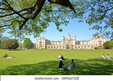 CAMBRIDGE, UK - MAY 6, 2018: Students enjoying a sunny day in a Park at St John's College University with New Court in the background
