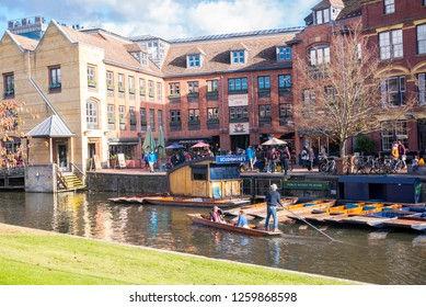 Cambridge, UK -  October 2018. Scudamore's Quayside Punting Station with tourists punting on the river Cam, view from with Magdalene College garden.