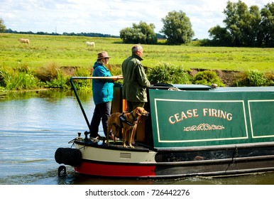 CAMBRIDGESHIRE, UK  - AUGUST 18, 2017: Couple with dog traveling on traditional narrow boat along Great Ouse river. Boating holidays are very popular with families and couples.