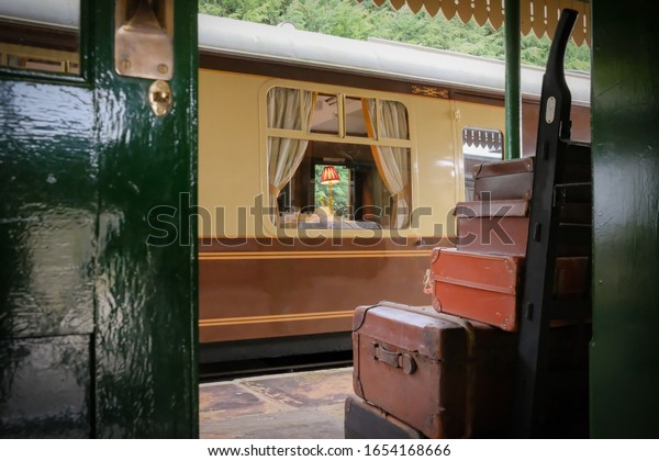 Cambridgeshire, UK - Circa February 2020: Framed view of a first class, old style dining railway carriage seen from the ticket off. Framed by old leather luggage, prior to departure.