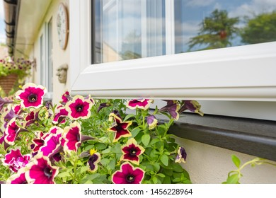 Cambridgeshire, UK - Circa July 2019:  Brand new installed double glazing windows seen installed on a house annex. A pretty flowering window basket is seen below the black window seal.
