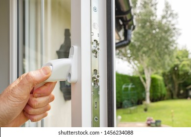 Cambridgeshire, UK - Circa July 2019: Person seen opening in a newly installed double glazed window on a house annex. Multiple locks can be seen on the window frame, seen adjacent to a large garden.