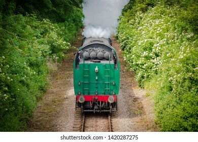 Cambridgeshire, UK - Circa June 2019: Fast approaching vintage steam locomotive with its coal tender seen head first. Large amount of steam can be seen flowing from the loco as it approaches a bridge.