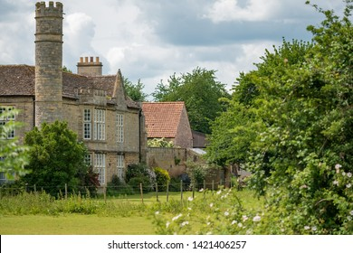 Cambridgeshire, UK - Circa June 2019: Detailed, majestic view of an unusual, Grade 2 listed, stone built manor house. Showing its usual single tower and large, picturesque garden in the foreground.