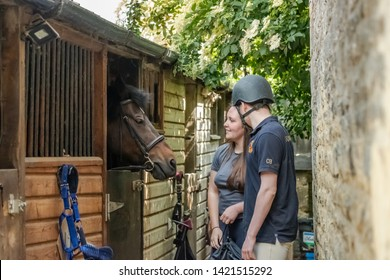 Cambridgeshire, UK - Circa June 2019: Pair of University students seen tending there New Forest Pony at a livery yard in the east of England. The young man is wearing a riding helmet, ready for a ride