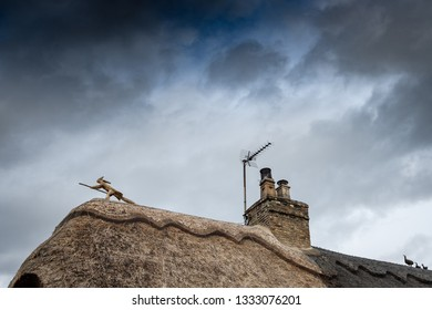 Cambridgeshire, UK - Circa March 2019: Detailed view of a new thatched roof within an english village. A signature straw hare riding a broomstick is visible on the roofs apex, unique to the thatcher.