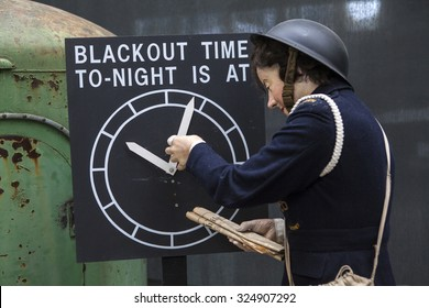 CAMBRIDGESHIRE, UK - OCTOBER 5TH 2015: An Air-raid Warden mannequin adjusting the blackout time at the Imperial War Museum Duxford in Cambridgeshire, on 5th October 2015.