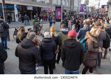 Camden, London / UK - Febuary 2 2019: Male guitarist busking in Camden Town with crowd onlooking.