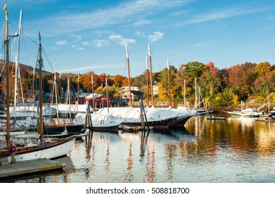 Camden, Maine harbor with bright fall foliage in autumn. Boats are being covered in anticipation for winter.