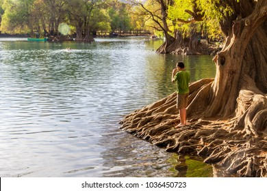 Camecuaro, Michoacan / Mexico - February Circa 2017: A kid stands on the shore of the Camecuaro lake. This is a very touristic place in the state.