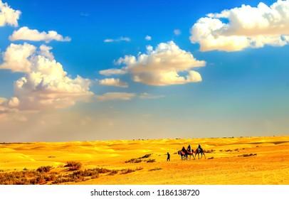 Camel caravan on sand desert landscape. Camel caravan desert sand dunes scene. Desert sand dunes camel caravan. Camel caravan desert sand dunes view