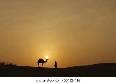 A camel & a people & desert of sunset