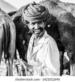 Camel trader in red pagadi (Turban) smiling during the Pushkar camel fair : Pushkar, Rajasthan/India - Oct 2017