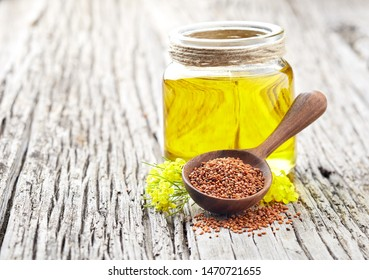 Camelina sativa oil with sedds and flowers on wooden background