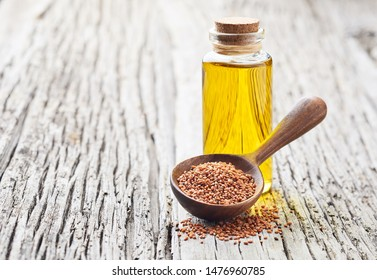 Camelina sativa oil. Wild flax oil with seeds on wooden background
