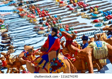 Camels made of leather with colorful dressed horsemen on a souvenir market in Marrakech Morocco