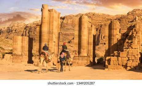 Camels transporting tourists in front of the Temenos Gate,  Petra Jordan