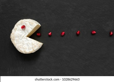 Camembert or brie cheese cut out like pacman eating pomegranate seeds on black slate background. Funny game with food. top view
