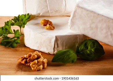 Camembert and brie cheese on cutting board on white background