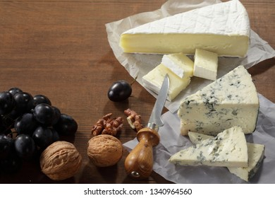 Camembert, brie, gorgonzola and blue mold cheeses on cheese board. Flat lay,