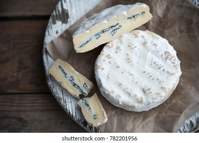 camembert cheese with blue mold on the wooden background