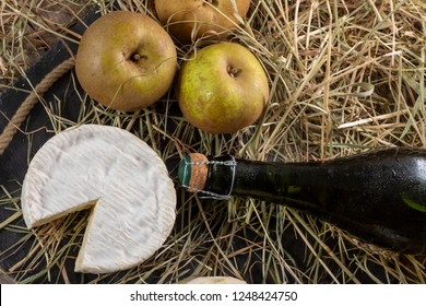 Camembert cheese, a bottle of cider and apples