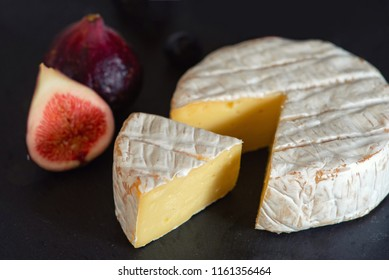 camembert cheese with figs and blueberries on on dark background.
