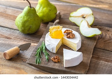Camembert cheese with fresh pears and walnuts on the wooden board