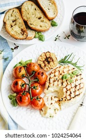 Camembert cheese fried on a grill with tomatoes and croutons. Red wine