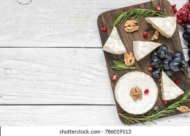camembert cheese with grapes, pomegranate seeds, walnuts and rosemary on wooden cutting board. top view with copy space