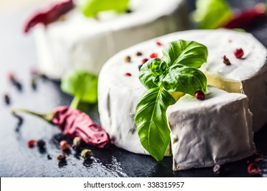 Camembert cheese on a granite board with basil leaves four colors pepper and chili peppers.