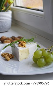 Camembert cheese on a plate with nuts and grapes